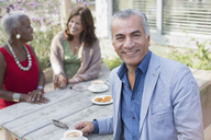 Portrait smiling senior man drinking coffee with friends at patio table - CAIF05663