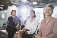 Smiling businesswomen listening in meeting - CAIF05669