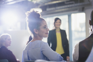 Businesswoman turning, listening in conference audience - CAIF05699