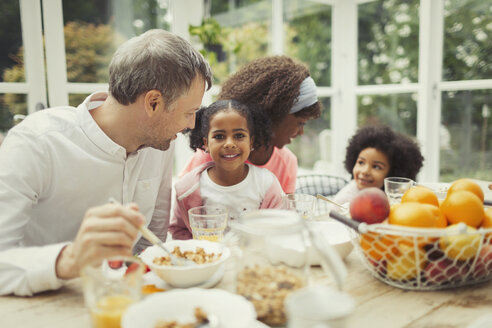 Portrait smiling multi-ethnic young family eating breakfast at table - CAIF05714