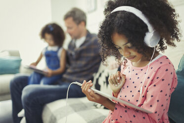 Girl with headphones using digital tablet on sofa - CAIF05717
