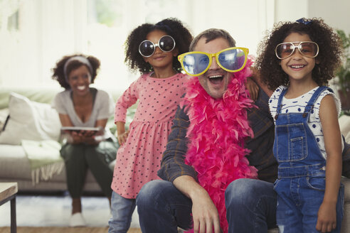 Portrait playful multi-ethnic father and daughters playing dress up with sunglasses and feather boas - CAIF05723