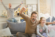 Male gay parents and children watching sports and cheering - CAIF05735