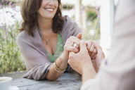 Close up affectionate mature couple holding hands at patio table - CAIF05744