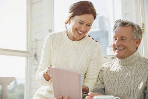 Smiling mature couple using digital tablet on sunny porch - CAIF05747