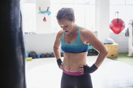 Tired female boxer resting with hands on hips in gym - CAIF05789