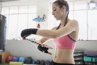 Young female boxer wrapping wrists in gym - CAIF05813