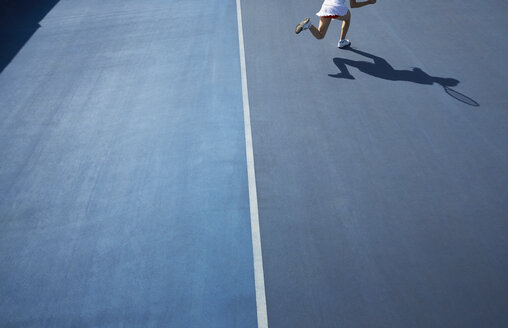 Shadow of female tennis player running on sunny blue tennis court - CAIF05822