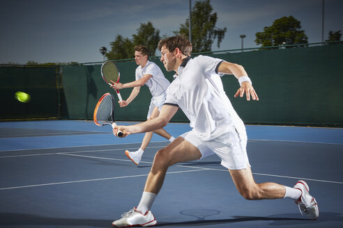 Young male tennis doubles players playing tennis, hitting the ball on blue tennis court - CAIF05837