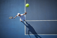 Overhead view of young male tennis player playing tennis, serving the ball on sunny blue tennis court - CAIF05840