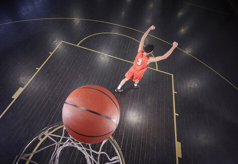 Confident young male basketball player shooting the ball and gesturing, celebrating - CAIF05858