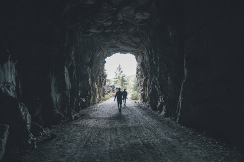 Canada, British Columbia, Kelowna, Myra Canyon, hikers on Kettle Valley Rail Trail crossing a tunnel - GUSF00425
