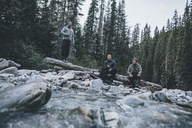 Canada, British Columbia, Glacier National Park, three friends at Illecillewaet River in forest - GUSF00431