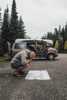 Canada, British Columbia, man with minivan reading map on highway - GUSF00440