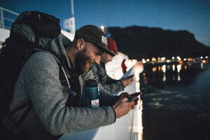 Canada, British Columbia, two men on a boat using cell phones at night - GUSF00455