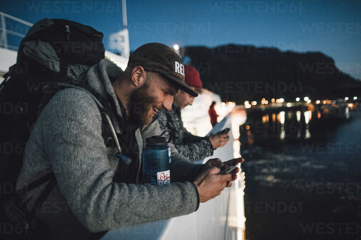 Canada, British Columbia, two men on a boat using cell phones at night - GUSF00455 - Gustafsson/Westend61