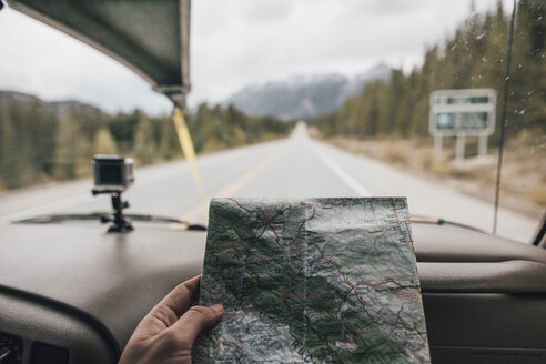 Canada, man in car reading map on highway - GUS00470