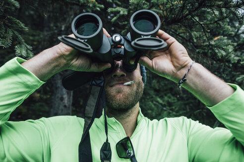 Man smoking a cigarette looking through binoculars in nature - GUSF00473
