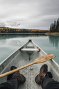 Canada, British Columbia, legs of a man in canoe on Boya Lake - GUSF00497