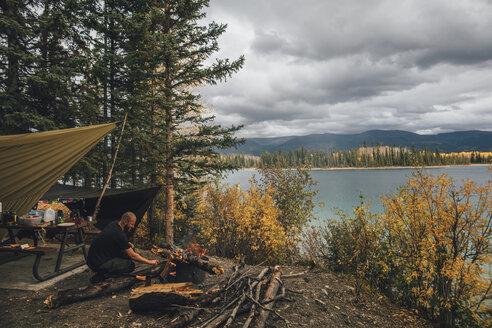 Canada, British Columbia, man making camp fire at Boya Lake - GUSF00503