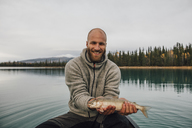 Canada, British Columbia, portrait of smiling man in canoe holding fish on Boya Lake - GUSF00512