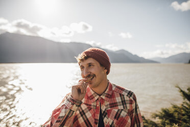 Canada, British Columbia, portrait of smiling man eating a cookie - GUSF00515