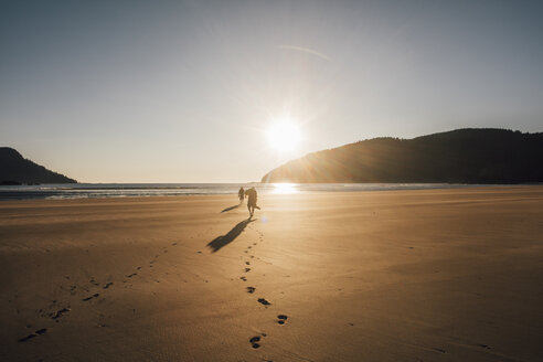 Canada, British Columbia, Vancouver Island, two men walking on beach at San Josef Bay at sunset - GUSF00527