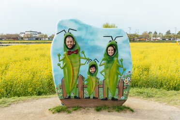 South Korea, Gyeongju, Family behind picture wall with grasshoppers, rape field in the background - GEMF01903