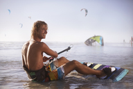 Smiling man ready to kiteboard on beach - CAIF05867