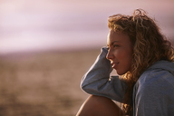 Pensive woman looking away on beach - CAIF05873