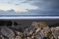 Seascape view behind rocks below overcast sky, Devon, United Kingdom - CAIF05912