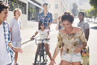 Teenage girl laughing with friends on sunny urban street - CAIF05933