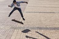 Teenage boy flipping skateboard on sunny cobblestone - CAIF05936