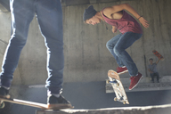 Teenage boy flipping skateboard at skate park - CAIF05939