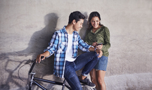 Teenage couple with BMX bicycle texting with cell phone at wall - CAIF05942