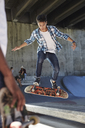Focused teenage boy flipping skateboard at skate park - CAIF05951