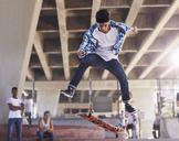 Friends watching teenage boy flipping skateboard at skate park - CAIF05960