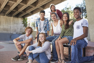 Portrait confident teenage friends hanging out at skate park - CAIF05963