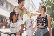 Teenage girls with BMX bicycle and skateboard on sunny urban street - CAIF05966