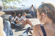 Teenage friends hanging out skateboarding at sunny skate park - CAIF05981