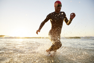 Male triathlete swimmer in wet suit running from ocean - CAIF05999