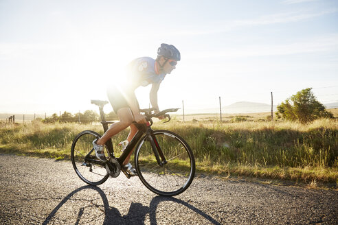 Male triathlete cyclist cycling on sunny rural road at sunrise - CAIF06014