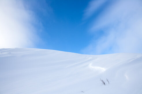 Snow-covered hill under blue sky - CAIF06020