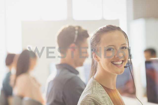Portrait smiling female telemarketer wearing headset in office - CAIF06032