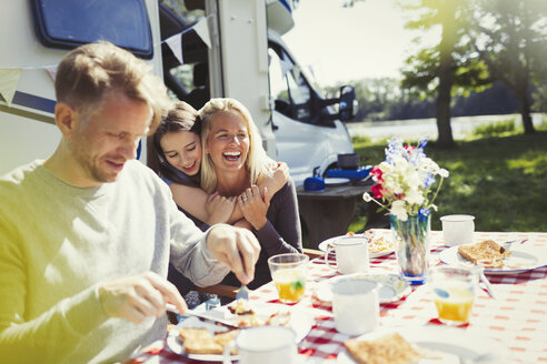 Happy family hugging and eating breakfast outside sunny motor home - CAIF06056