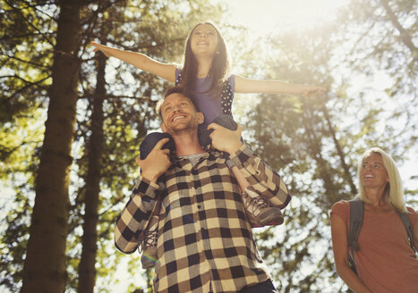 Father carrying daughter on shoulders, hiking in sunny woods - CAIF06065