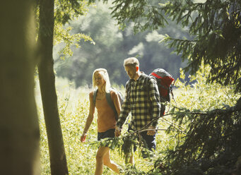 Couple with backpacks hiking in sunny woods - CAIF06071