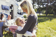 Affectionate mother and daughter hugging outside sunny motor home - CAIF06077