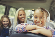 Portrait smiling girl wearing headphones in back seat of car - CAIF06086