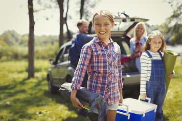 Portrait smiling family unloading camping equipment from car - CAIF06089
